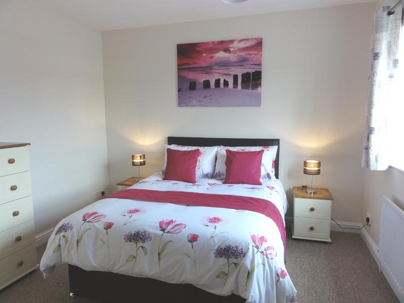 Large bedroom with king sized bed and large fitted wardrobes